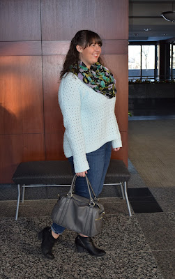 an outfit with a mint sweater, jeans, black booties, and a black floral scarf