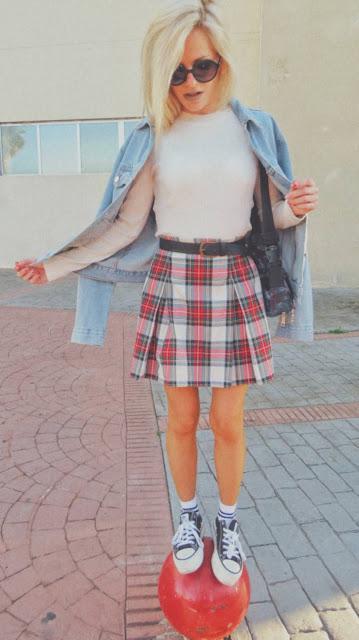 Estilo de los años 90 inspirado en Jennifer Aniston en Friends con suéter blanco, falda de tablas cuadros escoceses, zapatillas y calcetines blancos con raya negra