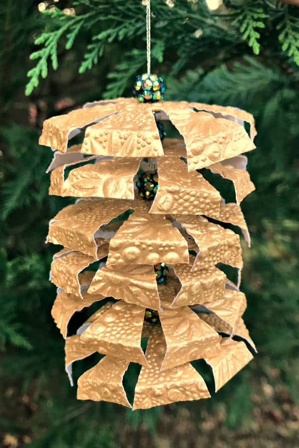 tiered gold embossed paper ornament with decorative beads hanging in evergreen tree