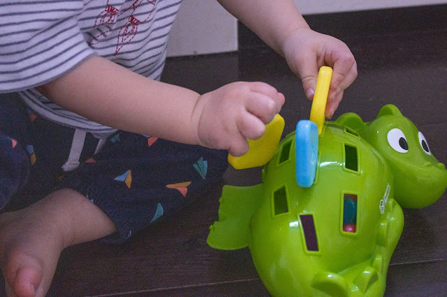 A 1 year old pulling out chunky colourful spikes from a green plastic dinosaurs back