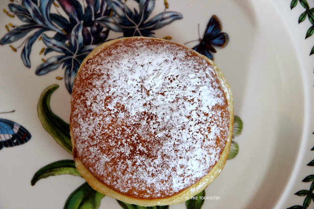 A jam doughnut dusted in icing sugar on a nicely decorated porcelain plate.