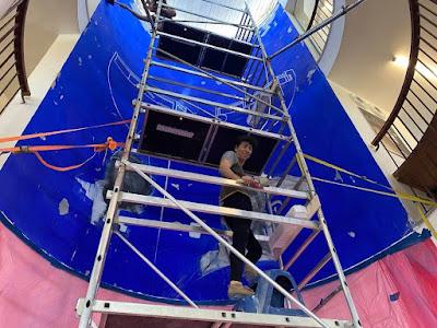 """משקמים את הציור הגדול של תמר גטר מתערוכת """"ארט פוקוס"""" 1994. תמר על הפיגום שהציב שי פרקש בבניין ההיסטורי המשופץ שתכנן מסטצ'קין עבור ספריית התנועה בגבעת חביבה."""