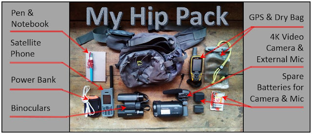 Equipment and hip pack all laid out on the floor: pen and notebook, satellite phone, power bank, binoculars, GPS and drybag, 4K video camera and external microphone, spare batteries for camera and microphone