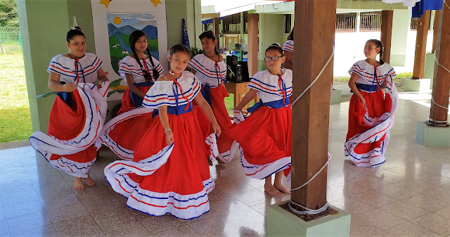 Students dancing in traditional dresses.