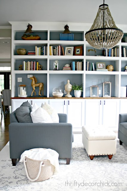 White DIY bookcases with smokey blue backs