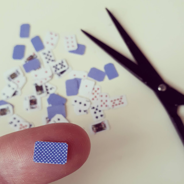 Finger with a one-twelth scale playing card on it. Behind the finger, on the work area, are the rest of the pack of cards and a pair of fine scissors