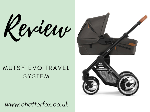 Image title reads review mutsy evo travel system image to the right is of a black framed travel system with a dark grey carry cot and a cognac leather handle