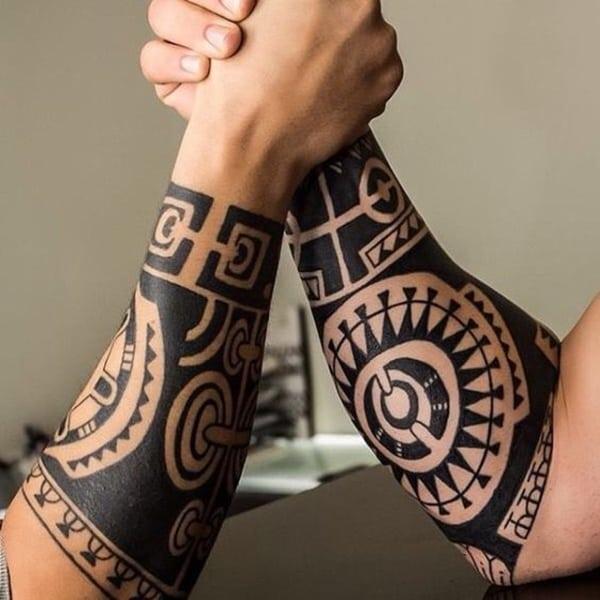 Imagen de dos brazos con tatuajes maories  echando un pulso