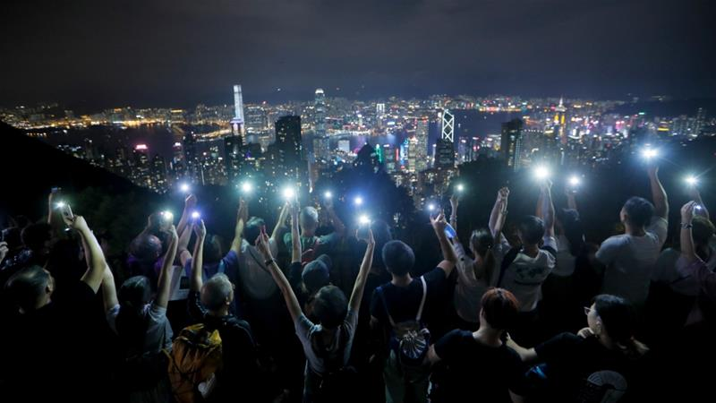 Hong Kong protesters light up hills in festival-themed rally