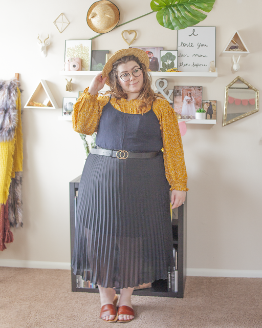 An outfit consisting of a yellow microfloral long sleeve off the shoulder blouse under a thin strap black dress tucked into a black pleated midi skirt and brown slide sandals.