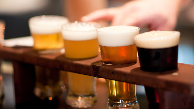 four small glasses of various beers