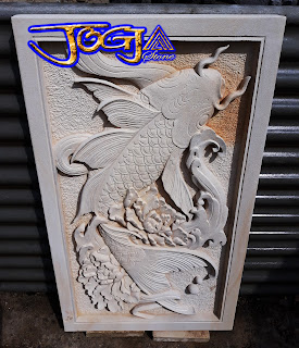 Ukiran relief gambar timbul motif ikan hias dari batu alam paras jogja atau batu putih
