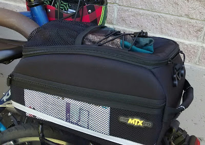 Trunk bag secured to rear bike rack. A portion of the bike's rear tire is visible beneath. A folded paper is tucked inside the trunk bag's mesh side pocket and a rolled up hat is tucked into a mesh pocket and bungee cords on the top of the bag. In the upper left, the image includes a portion of a bike rack and the frame of a second bike and helmet.