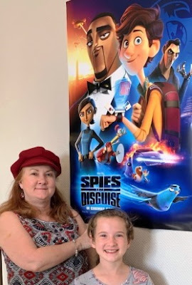 Karen du Toit pose in front of Spies in Disguise poster
