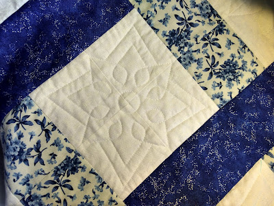 Detail of qilting motif on blue and white patchwork quilt