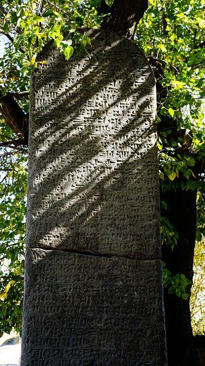 Antigua escritura cuneiforme grabada sobre una roca.
