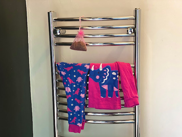 A silver ladder style heated towel rail with Children's Pink Dinosaur Pyjamas warming on them