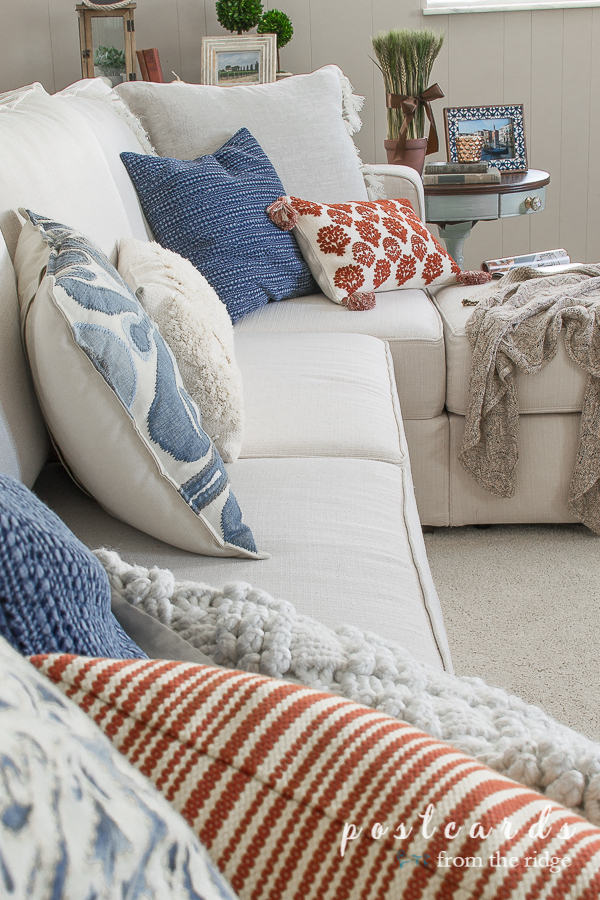 blue and orange pillows on an off white sectional sofa