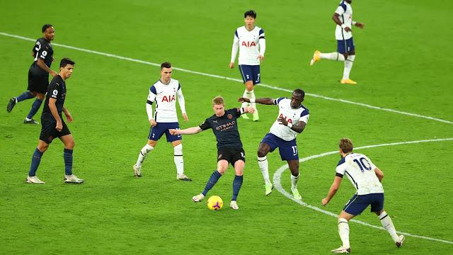 Tottenham players surround Man city midfielder Kevin De Bruyne