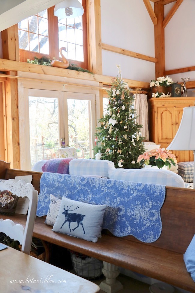 French country Christmas living room tour includes a view of a vintage church pew used as extra seating for the dining table