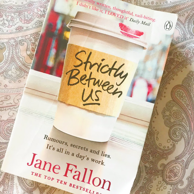 Strictly Between Us by Jane Fallon book at an angle on pink patterned background