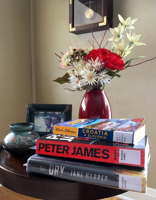 sidetable with three books, and a vase of flowers, and a clock on the wall behind.