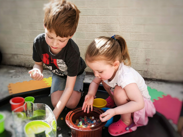 A blonde haired boy and girl are sat inside a large black tray surrounded by jugs, small pots, glasses, a tall round ceramic dish and other containers with small round colourful water beads inside. They are leaned over, playing with a white brick wall behind them.
