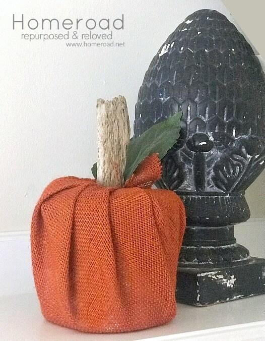 Orange burlap pumpkin next to a black artichoke sculpture.