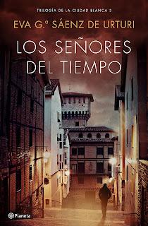 Portada del libro Los señores del tiempo de Eva García Sáenz de Urruti con la editorial Planeta. Muestra una calle de Álava por la noche y un hombre caminando de espaldas.