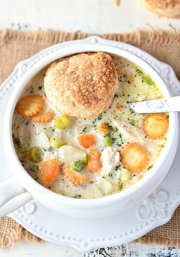 biscuit topped with a white bowl full of creamy chicken pot pie soup