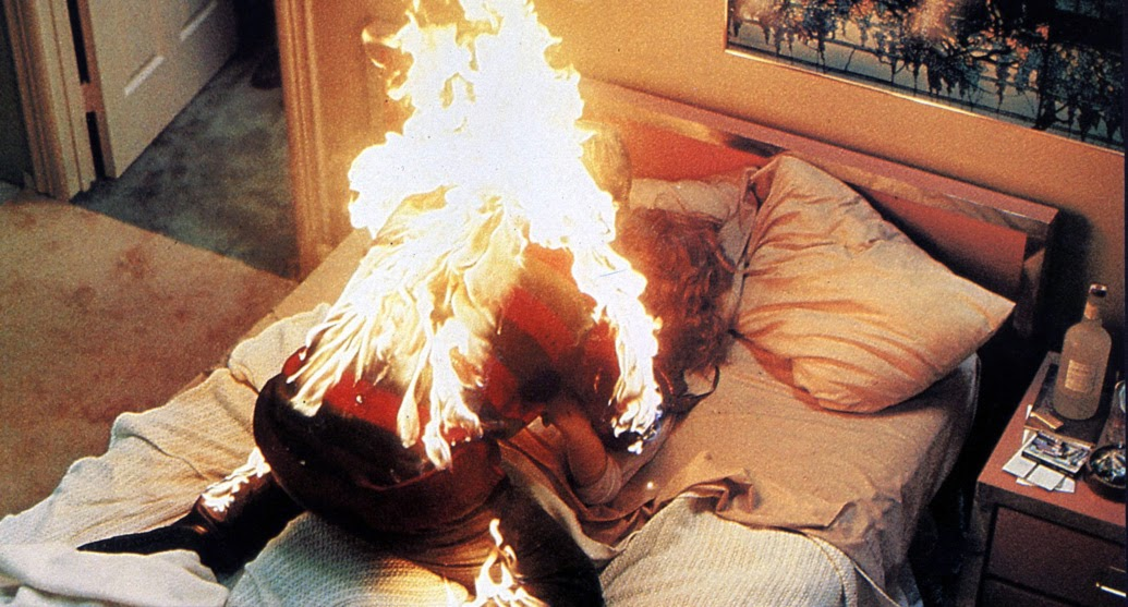Freddy Krueger is on fire killing the mother in bed.