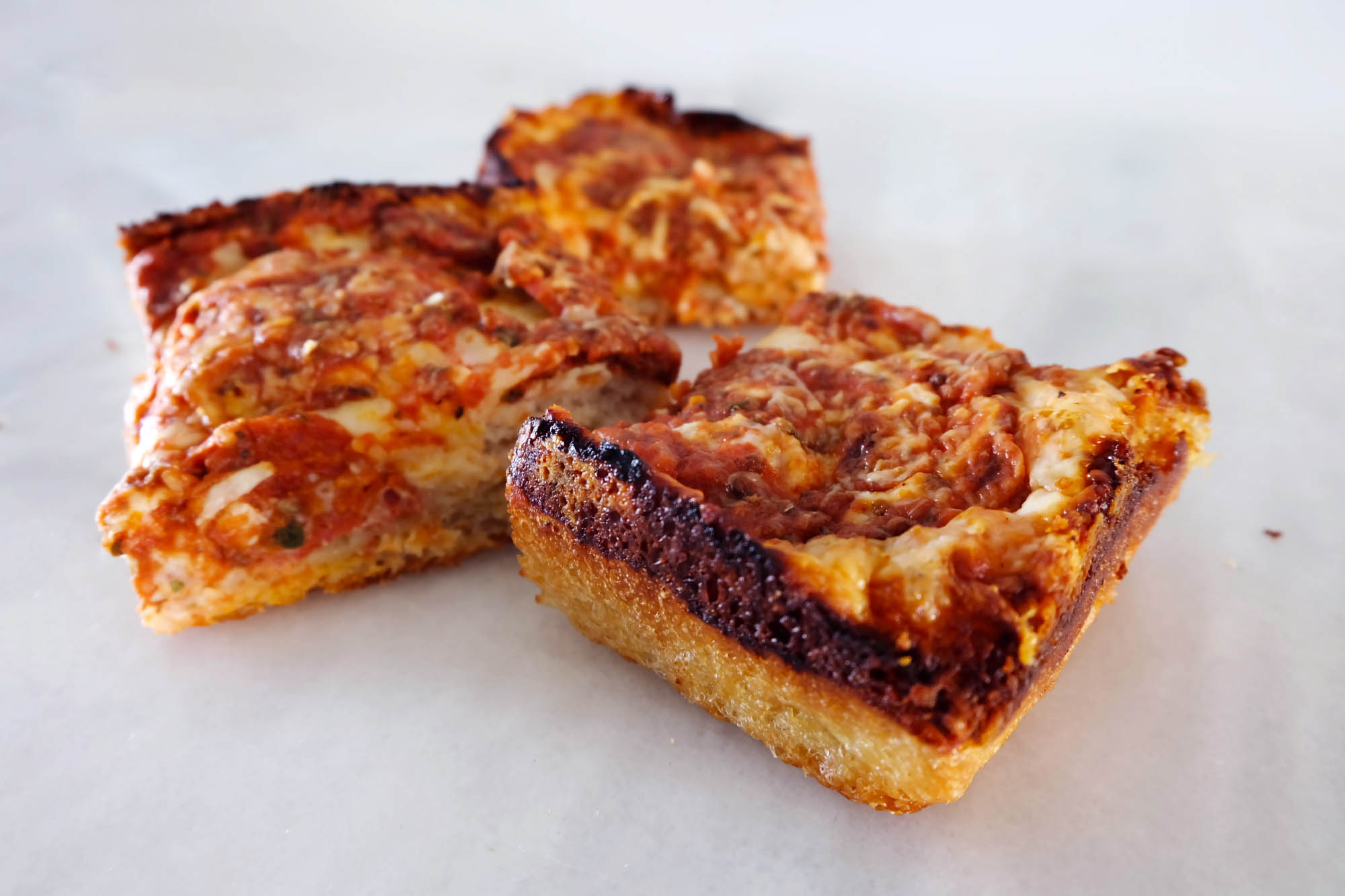 slices of pan pizza with burnt cheese edge