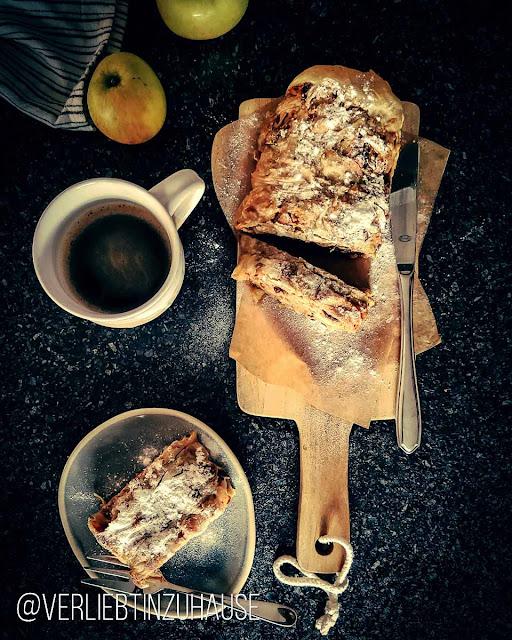 Auf einem Holzbrett liegt ein Wiener Apfelstrudel mit Puderzucker bestäubt