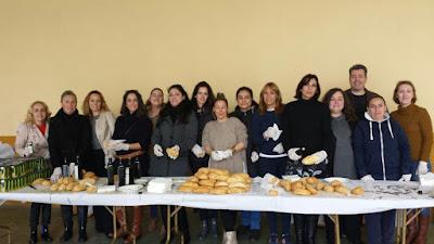 Un grupo de madres y padres colaborando en el desayuno andaluz.