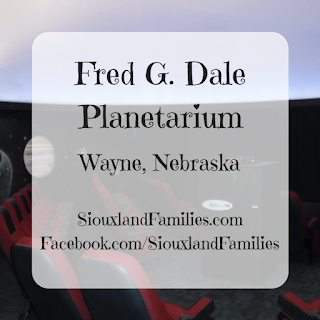 "in background, a round room with black walls painted with a moon and stars on them is filled with red and black theater seats and the bottom of a white dome is visible. in foreground, the words ""Fred G. Dale Planetarium Wayne Nebraska"" and ""SiouxlandFamilies.com Facebook.com/SiouxlandFamilies"" sit on a translucent white square."