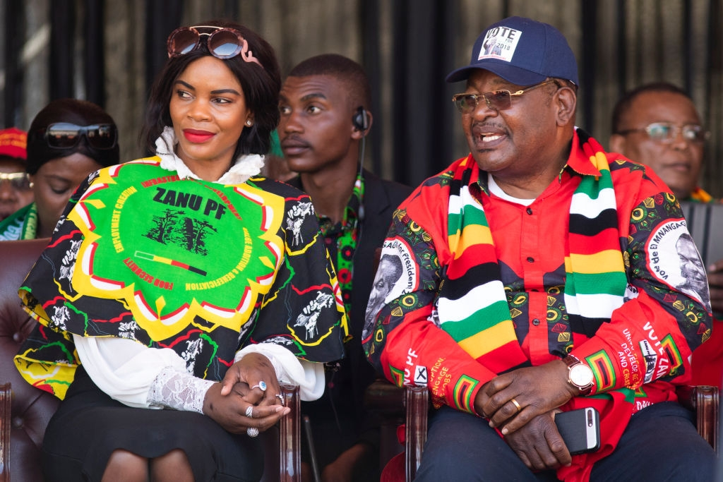 Wife of Former defence force commander General Constantino Chiwenga, Mary Chiwenga, (left) and Home Affairs minister Obert Mpofu listen as Zimbabwe's President Emmerson Mnangagwa delivers his closing presidential campaign at the National Sports Stadium during his final 'Zimbabwe African National Union-Patriotic Front' (Zanu PF) rally on July 28, 2018 in Harare, Zimbabwe. Zimbabweans go to the polls on July 30th to vote for a new president, the first since the end of Robert Mugabe's 37-year rule. (Photo by Dan Kitwood/Getty Images)