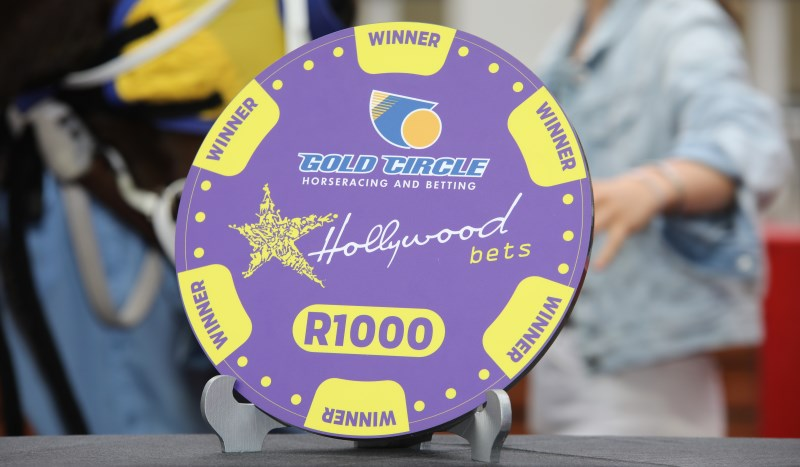 Grooms' Initiative R1000 Token with Gold Circle and Hollywoodbets branding