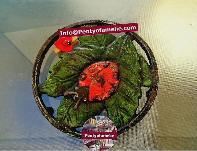 vintage french rare round cast iron trivet with green leaf and a lovely red lady beetle design