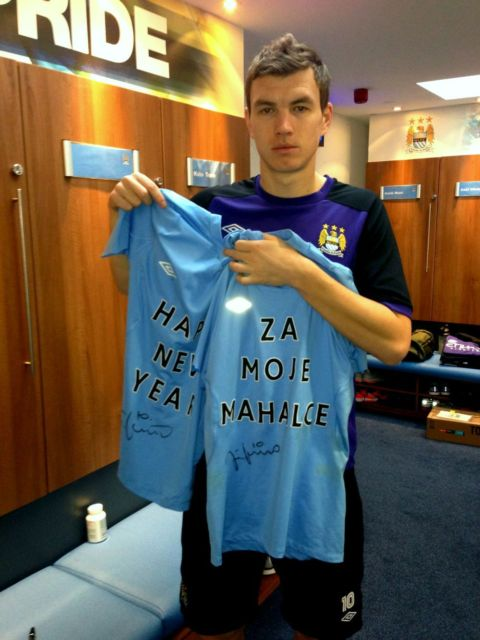 Edin Džeko poses with the undershirts he sells for charity