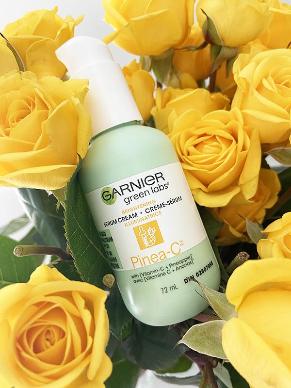 A bottle of Garnier Brightening Serum Cream Pinea-C SPF 30 lies nestled in a bouquet of yellow roses.