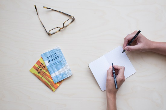 Two pale-skinned right hands hold pens poised to write or draw on a blank notebook laid open on a pale wood table. One of the hands sports peach nail polish. Two more notebooks, one blue and white and one orange and yellow, are positioned nearby, along with a pair of tortoiseshell glasses.