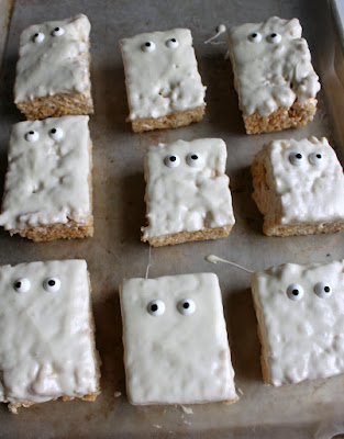 tray of white chocolate dipped rice crispy treats with eyeballs, looking like ghosts