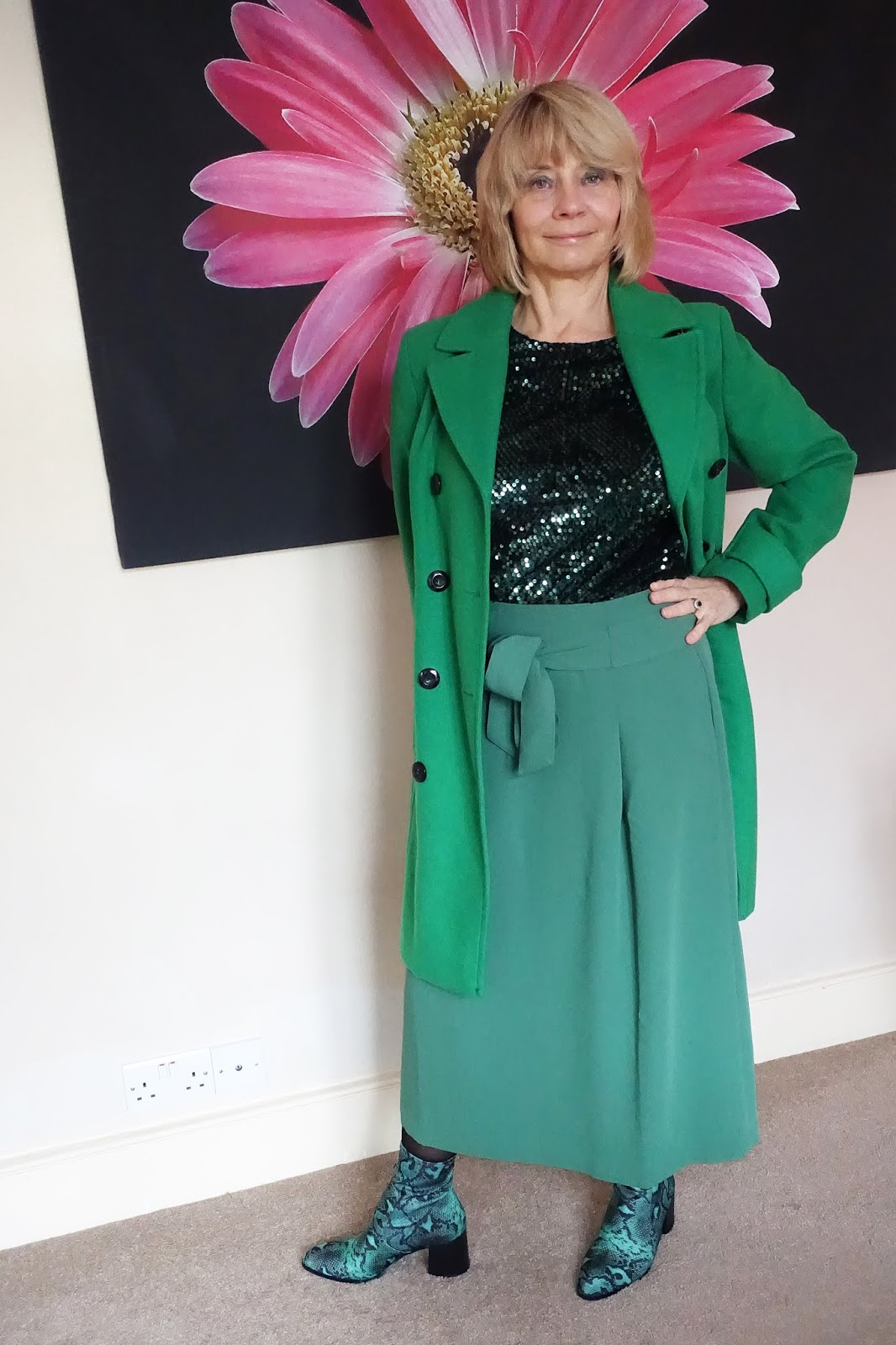 A green coat, green midi skirt, green sequinned top and green snakeskin boots provide tonal contrast in a monchrome outfit worn by over-50s blogger Gail Hanlon from Is This Mutton?