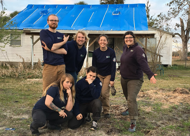 Six people gather for a photo in front of a house with a large blue tarp installed on the roof. Five are AmeriCorps members wearing blue shirts, and one is the crew supervisor wearing a purple sweatshirt.