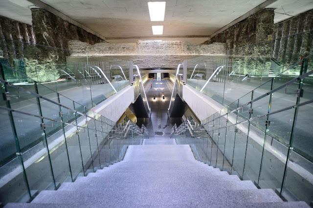 Escaleras dentro de la estación de metro, con vista a las ruinas arqueológicas a ambos lados y viga grande transversal