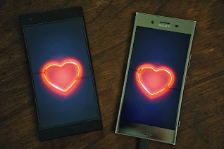 Two cellphones with a love sign to represent virtual love
