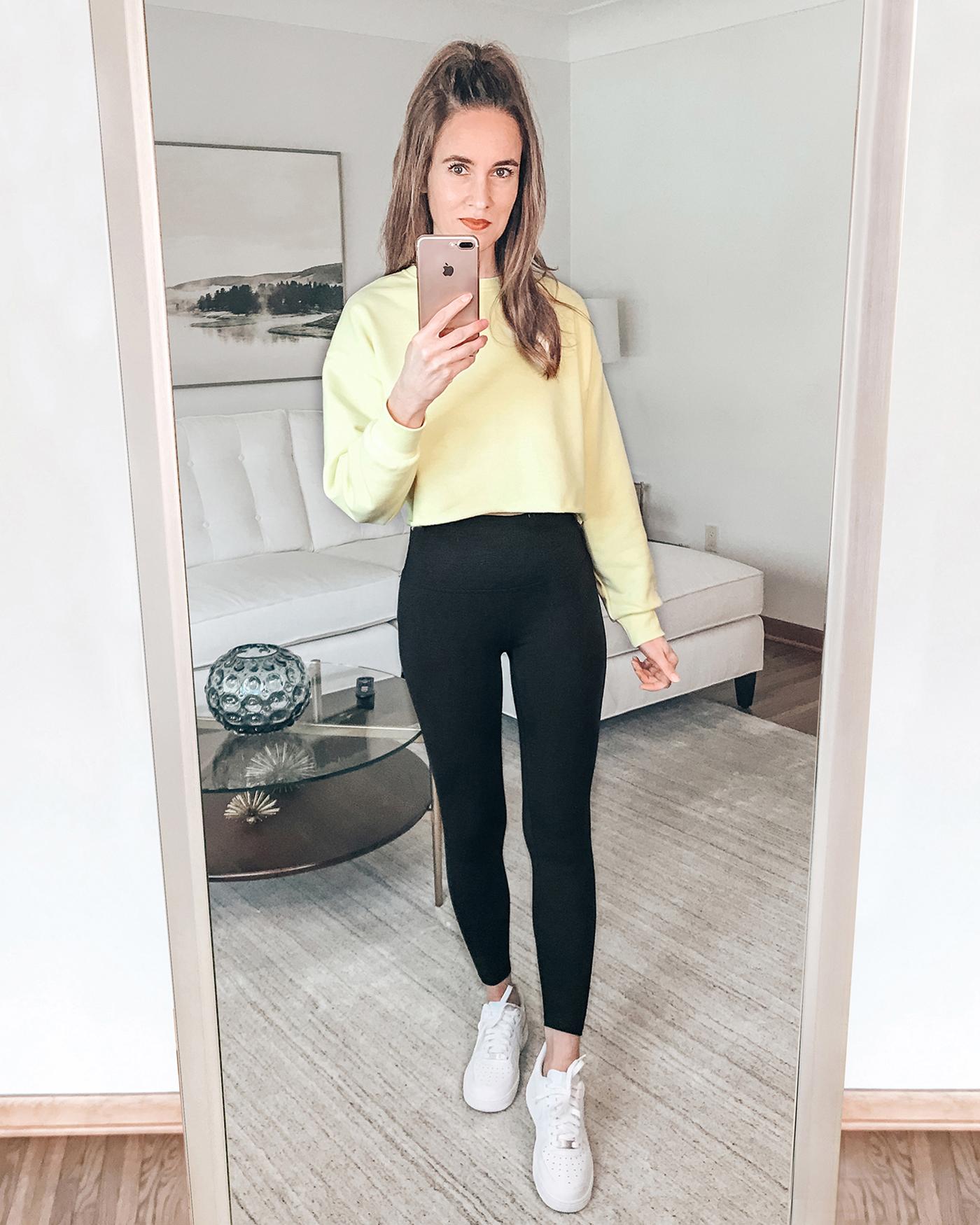 yellow crop sweatshirt, black leggings, white Nike Air Force 1 Sneakers