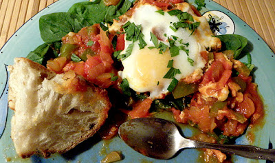 Plate with half-eaten shakshuka and bread portion