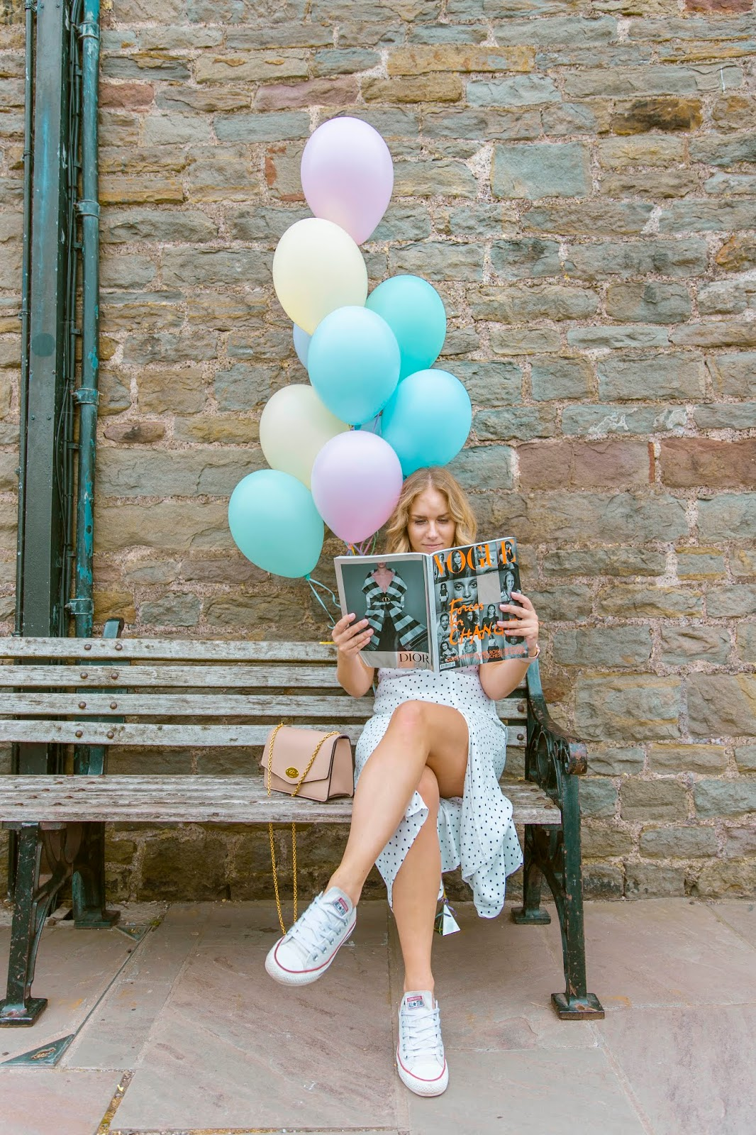 Rachel Emily on a bench in a white dress reading Meghan Markle's Vogue Issue with pastel coloured balloons in the background
