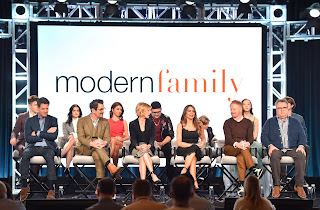 """The whole cast of TV Sitcom Comedy """"Modern Family"""" being interviewed under a backdrop of the show's logo."""